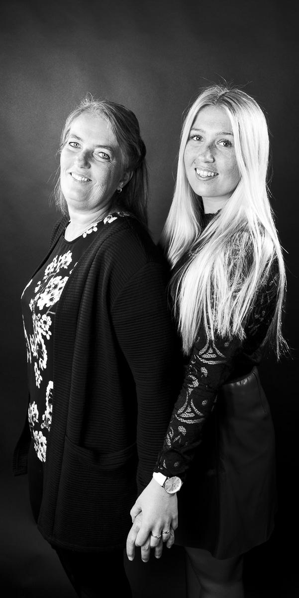 Sanne en Annelies studioportret in zwart-wit op een donkere achtergrond