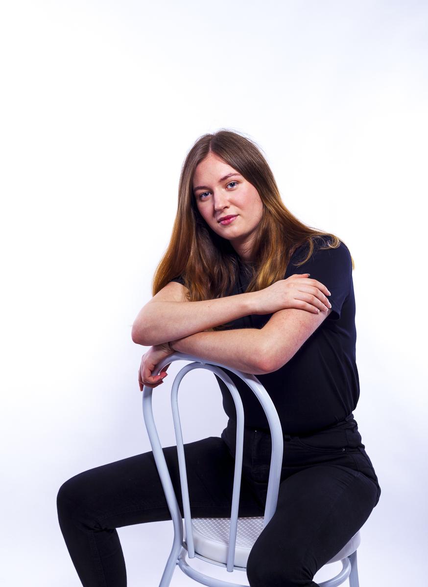 Dana Portfolio Photoshoot posing on a chair