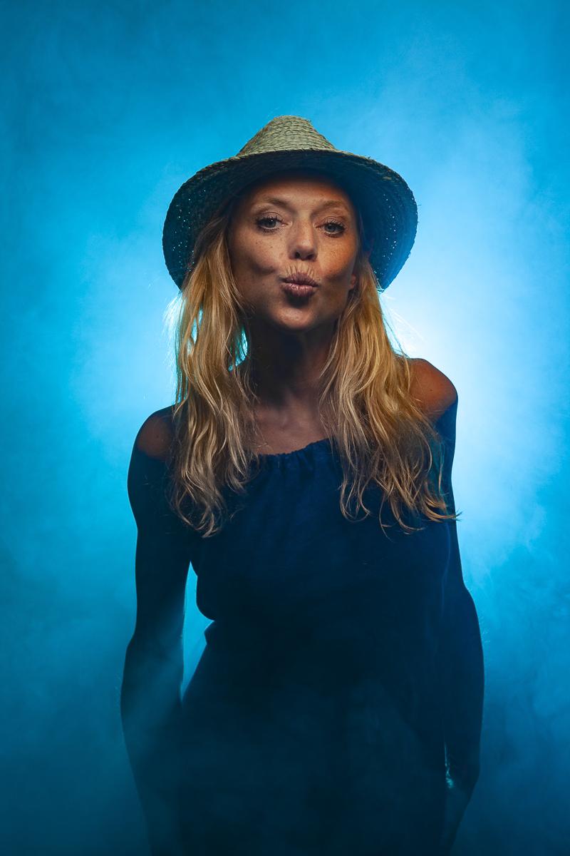 Leonor Studioportret met hoedje, rook en blauw licht